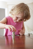 Girl putting coins Stock Photos