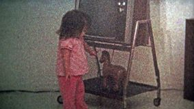 1973: Girl putting coins in piggy bank under the vintage tv. stock footage