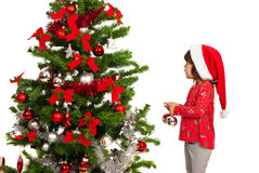 Girl putting colorful balls in tree Royalty Free Stock Image
