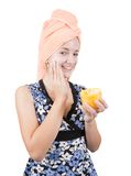 Girl putting cream on her face over white Royalty Free Stock Image