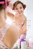 Girl putting curlers in hair Stock Images