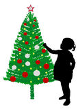 Girl putting decoration on christmas tree Royalty Free Stock Photography