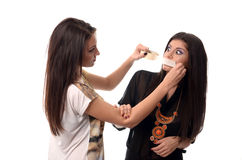 Girl putting duct tape over her friends mouth Royalty Free Stock Images