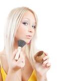 Girl putting facial powder Stock Image