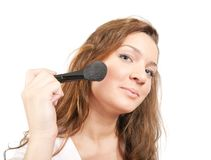 Girl putting facial powder  with a brush Royalty Free Stock Photography