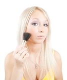 Girl putting facial powder on her face Royalty Free Stock Photos