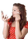 Girl putting facial powder on her face Royalty Free Stock Images