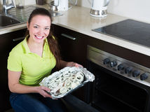 Girl putting fish in oven Royalty Free Stock Images