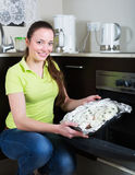 Girl putting fish in oven Stock Photos