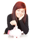 Girl putting five euro in piggy bank Royalty Free Stock Images