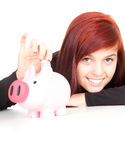 Girl putting five euro in piggy bank Stock Images