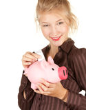 Girl putting five euro in piggy bank Stock Image