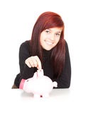 Girl putting five euro in piggy bank Royalty Free Stock Photo