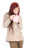 Girl putting five euro in piggy bank Stock Photo