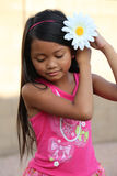 Girl Putting Flower In Hair Stock Photography