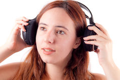 Girl Putting On Head Phones Stock Images