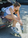 Girl putting on inline skates. Stock Images