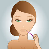 Girl putting on lip-gloss Stock Images