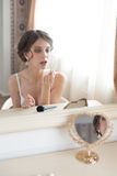 Girl putting on lip gloss Royalty Free Stock Photography