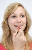 Girl putting on lipstick Stock Photography