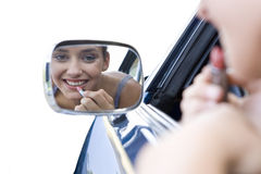 Girl putting on lipstick in car mirror, cut out Stock Photos