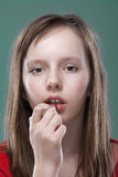 Girl putting on makeup Royalty Free Stock Photography
