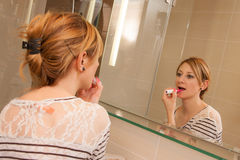 Girl Putting Makeup. Young pretty girl putting her makeup in front of a big mirror Stock Photos