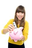 Girl putting money in piggy bank Stock Image