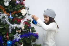 Girl putting ornament on Christmas tree Stock Photography