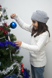 Girl putting ornament on Christmas tree Stock Images