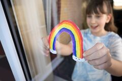 Free Girl Putting Picture Of Rainbow In Window At Home During Coronavirus Pandemic To Entertain Children Stock Image - 176794941
