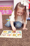 Girl putting a puzzle together Stock Images