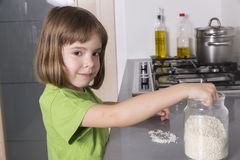 Girl putting rice in a glass container Royalty Free Stock Photos