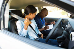 Girl putting seatbelt. Young african girl putting on seatbelt during a driving test stock photography