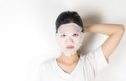 Girl in putting on a skin care paper mask Royalty Free Stock Image