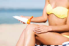 Girl putting sun protection cream on beach chair Royalty Free Stock Photos