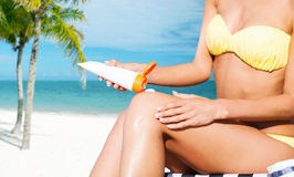 Girl putting sun protection cream on beach chair Stock Photos
