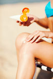 Girl putting sun protection cream on beach chair Stock Photo