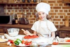 Girl putting tomato sauce on pizza dough Stock Image