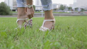 A girl putting on wedges on the grass. stock footage