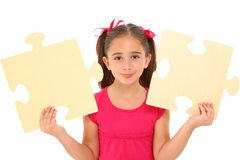 Girl with Puzzle Pieces. Beautiful 7 year old girl holding two large puzzle pieces over white background royalty free stock photos