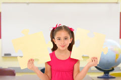 Girl with Puzzle Pieces. Beautiful 7 year old girl holding two large puzzle pieces in school classroom royalty free stock photo