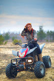Girl quad. Girl with red hair sitting on an ATV Stock Photo
