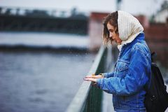 Girl on the quay in the rain beats hands on the railing forming splashes Stock Image