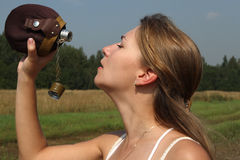 The girl quench thirst. With flask in the outdoor Stock Photography