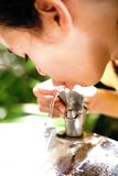 Girl quenching thirst at water cooler Stock Images