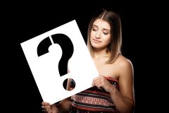 Girl with a question mark sign. Beautiful young girl holding a question mark sign Royalty Free Stock Images