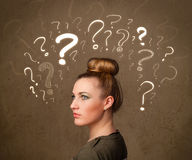 Girl with question mark symbols around her head Royalty Free Stock Photos