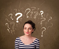 Girl with question mark symbols around her head Royalty Free Stock Image