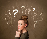 Girl with question mark symbols around her head Royalty Free Stock Photography